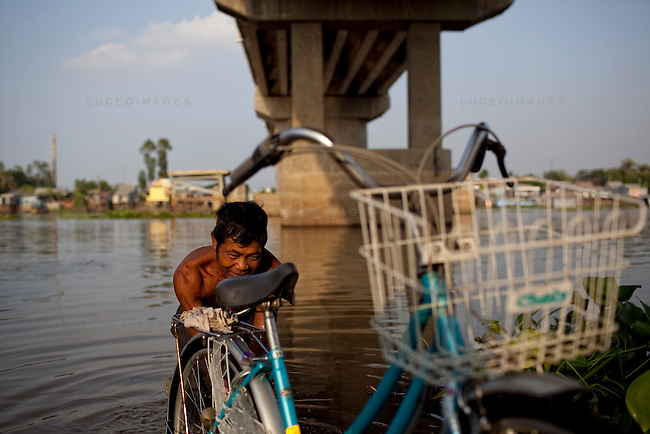 """Sao, 49, washes his bicycle in the Hau Giang River, a tributary of the Mekong River, in Chau Doc, in the An Giang Province, Vietnam. When the Mekong River reaches Vietnam it splits into two smaller riveres. The """"Tien Giang"""", which means """"upper river"""" and the """"Hau Giang"""", which means """"lower river"""". Photo taken on Monday, December 7, 2009. Kevin German / Luceo Images"""