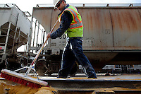 Los Angeles, California, March 1, 2010 - Emilio Razo cleans the transport lines along the rails for the next freight load of sugar beet pellets destined for Korea and Japan at the Los Angeles Harbor Grain Terminal. Demand for U.S. products is spiking in Asia, thanks to a weak dollar and quicker economic recovery. However, decline in U.S. consumption has left exports short of a good exit strategy. In 2009, imports fell 28%. This has created a bottleneck for exports, which need the shipping containers to move product overseas. ...
