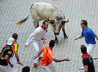 Participants run with Torrestrella fighting bulls during the fifth San Fermin Festival´s running of the bulls, on July 11, 2013, in Pamplona, Basque Country. On each day of the eight San Fermin festival days six bulls are released at 8:00 a.m. (0600 GMT) to run from their corral through the narrow, cobbled streets of the old navarre town over an 850-meter (yard) course. Ahead of them are the runners, who try to stay close to the bulls without falling over or being gored. (Ander Gillenea / Bostok Photo)