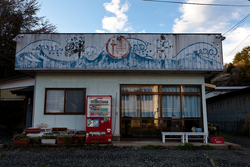 An empty restaurant with a tsunami painting on its sign in the abandoned village of Tsushima in Fukushima, Japan. Friday May 4th 2012. After the explosions at the Daichi nuclear plant caused by the March 11th 2011 earthquake and tsunami, High levels of radioactive contamination in this village have made it uninhabitable.