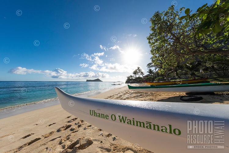 The sun rises over Waimanalo Beach and Bay, with outrigger canoes in the foreground and kayakers and Manana and Kaohikaipu Islands in the distance, Windward O'ahu.