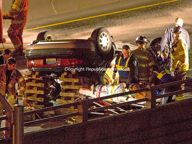 WATERBURY, CT- 13 JANUARY 2008-011308JS02--EMT's tend to the driver after being extractated from a vehicle involved in a rollover accident on I-84 westbound near exit 21 in Waterbury on Sunday afternoon.<br /> Jim Shannon / Republican-American
