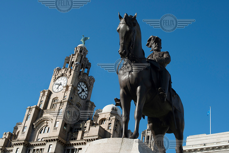 A statue of King Edward VII and the Royal Liver Building in Liverpool.