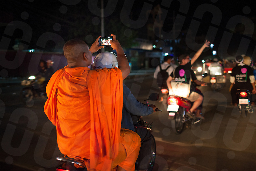 June 27, 2011 - Phnom Penh, Cambodia. Monk Loun Sovath records supporters celebrating the news that 13 imprisoned activists will be released on bail. © Nicolas Axelrod / Ruom