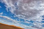 Desert sand dunes Erg Chebbi against cloudy blue sky, Merzouga, Morocco.