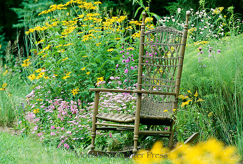 Handwoven rocking chair at the edge of the summer garden