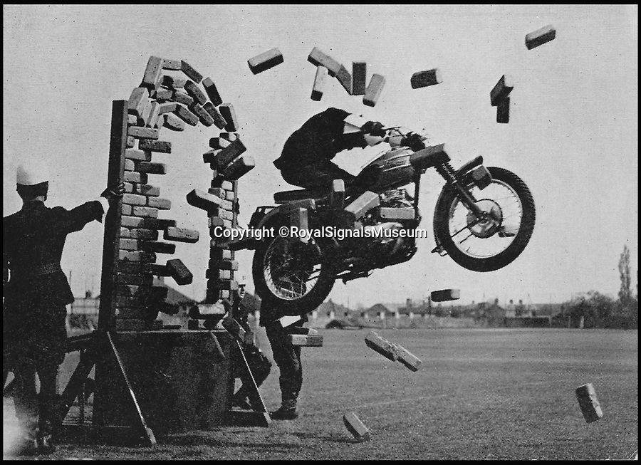BNPS.co.uk (01202 558833)<br /> Pic: RoyalSignalsMuseum/BNPS<br /> <br /> 1958, a White Helmet rider jumps through a wall.<br /> <br /> The iconic motorcycles used by the disbanded White Helmets are to be auctioned - but it is feared none of the riders will be able to afford to buy their beloved bikes.<br /> <br /> After the famous Army daredevil display team performed their last ever event in August, their 30 Triumph bikes were split up.<br /> <br /> The Army has given permission for six of them to be sold to the public at an auction in Sherborne, Dorset.<br /> <br /> Although the famous machines have been given pre-sale estimates of £6,000 each they are likely to fetch double if not treble that figure.