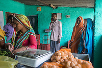 Jeevika Field Associate Jagganath Prasad (grey pants), coordinates with the local markets to purchase a top up of vegetables that is needed by the collection centre to be sold to their buyers in Muzaffarpur, Bihar, India on October 27th, 2016. Non-profit organisation Technoserve works with women vegetable farmers in Muzaffarpur, providing technical support in forward linkage, streamlining their business models and linking them directly to an international market through Electronic Trading Platforms. Photograph by Suzanne Lee for Technoserve