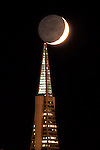A waxing moon seems to touch the Transamerica Pyramid in San Francisco as it moves through a fogless evening. The photo was taken from Treasure Island, San Francisco, California.