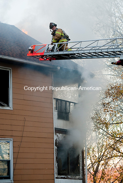 WATERBURY, CT--- -112015JS02--A firefighter waits for a ladder to be brought up after Waterbury firefighters were called out on Friday to battle a house fire at 46  St. Jean Street in Waterbury. <br />  Jim Shannon Republican-American