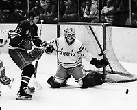 """Seals vs New York Rangers..Rangers Jean Ratelle and Seals goallie Gary Simmons """"The cobra"""" (1974 photo  by Ron Riesterer)"""