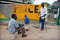 Painters paint the word Peace on a wall as they chat to a man who lost his leg during the civil war.