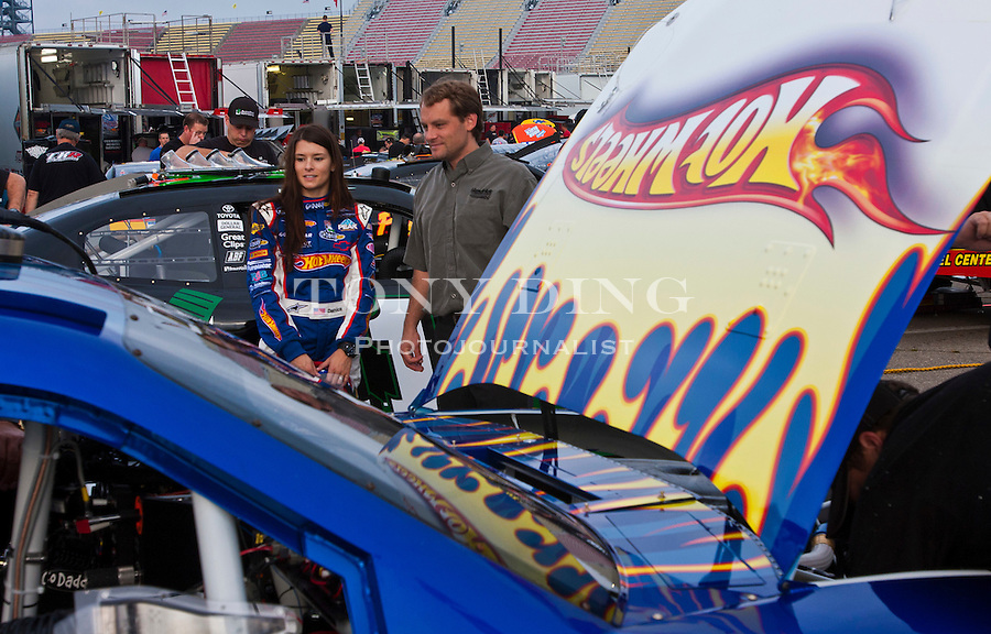 Danica Patrick, left, looks over her new Hot Wheels NASCAR racecar, featuring its iconic red and orange flames, Thursday, Aug. 12, 2010, at Michigan International Speedway in Brooklyn, Mich. Hot Wheels debutes its sponsored racecar, in a new format for the NASCAR Nationwide Series, at this weekend's CARFAX 250 Nationwide race. (Tony Ding/ AP Images for Mattel, Inc.)