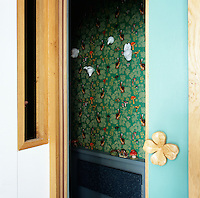 A view into the bathroom with it's green floral wallpaper studded with animal figures