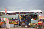 MAN AND BOY IN ROADSIDE FRUIT STAND
