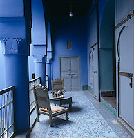 Locally crafted chairs on a first floor balcony of this Moroccan home has a tiled floor with a repeating pattern of eight tiles with stylized roses, inspired by old Iznik tiles in the souk