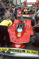 LONG BEACH, CA - APRIL 8: Gilles Villeneuve of Canada stands at the rear wing of his Ferrari 312T4 037/Ferrari 015 while the crew makes adjustments before practice for the United States Grand Prix West FIA Formula One World Championship race on the temporary Long Beach Street Circuit in Long Beach, California, on April 8, 1979.