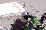 A man in a carriage on the streets of Marrakesh, Morocco waits for someone to ask for a carriage ride. .