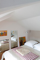 Paintings by Nigel Robinson and Carole Melmoux decorate this attic bedroom