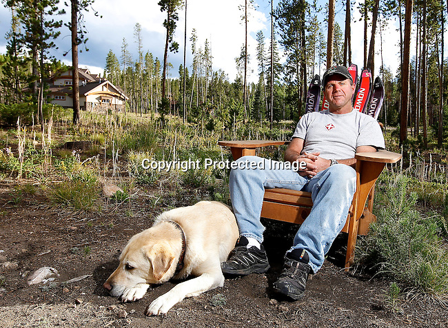 Custom homebuilder Bob Wolf and lifelong Winter Park ski patroller relaxes in the backyard with his dog Bailey.  One of the homes he built is in the background. (AP Photo/Margaret Bowles)