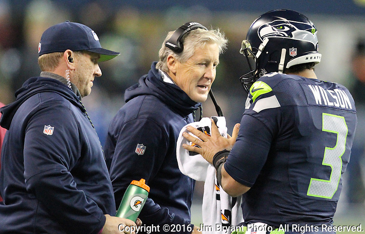 Seattle Seahawks head coach Pete Carroll, middle, confers with Seattle Seahawks quarterback Russell Wilson (3) during their game against the Carolina Panthers at CenturyLink Field in Seattle, Washington on December 4, 2016.  Seahawks beat the Panthers 40-7.  ©2016. Jim Bryant photo. All Rights Reserved.