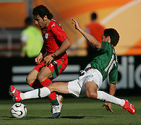 JUNE 11, 2006: Nuremberg, Germany: Mexican forward (10) Franco Guillermo tackles the ball away from Iranian midfielder Mehdi Mahdavikia during the World Cup Finals at Franken-Stadion in Nuremberg, Germany.  Mexico defeated Iran, 3-1.
