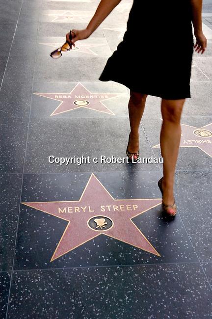 Woman walking along Hollywood Boulevard's Walk of Fame