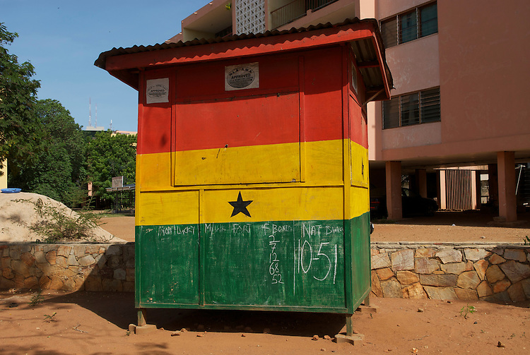 "Winning numbers in chalk. The kiosk is painted as the national flag: ""The Meaning of the Flag. I decided on the three colors of red, gold & green because of the geography of Ghana. Ghana lies in the tropics and blessed with rich vegetation. The color Gold was influenced by the mineral rich nature of our lands and Red commemorates those who died or worked for the country's independence. Then the five pointed lone star which is the symbol of African emancipation and unity in the struggle agianst colonialism."" Designer: Mrs. Theodosia Salome Okoh"
