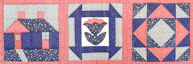 This three block panorama from a small hand-stitched quilt uses three traditional designs with the leftmost block containing a log cabin motif, which is also one of the few asymmetrical areas in the overall piece. The other two blocks are geometric with the center flower section based on four to build the pattern, and the rightmost block pattern is based on eight.<br />
