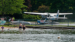 WINSTED,  CT-071919JS10--  Swimmers at Holland Beach on Highland Lake in Winsted looks on as A Cessna 208B Grand Caravan, registered with Galaxy Lift LLC of New York City, makes its way into the parking lot of the Highland Lake Boat Launch after landing on the lake on Saturday. <br /> Jim Shannon Republican American