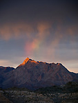 An ephemeral rainbow appears over an unnamed peak at sunset near the Colorado River and Lake Mead confluence in the Lake Mead National Recreation Area on the Arizona-Nevada border (Photo from Nevada)