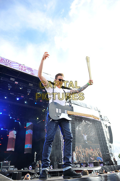 Danny Jones of McFly .performing at BT London Live, Hyde Park, London, England, .4th August 2012..music live on stage full length holding Olympic torch jeans guitar tattoos sunglasses white t-shirt .CAP/MAR.© Martin Harris/Capital Pictures.