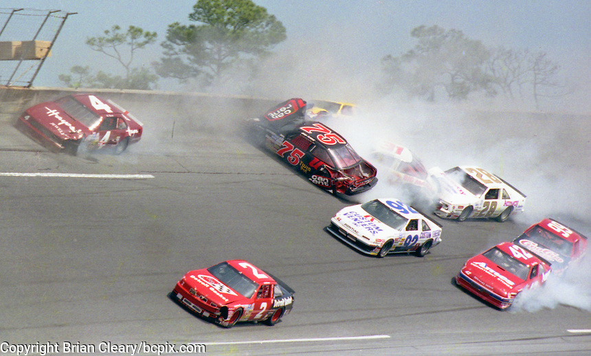 The cars of Tommy Ellis (99), Brad Teague (75), Hut Stricklin (28), Kyle Petty (42), Rick Mast (22), Steve Grissom (31), Michael Waltrip (30) , Tom Peck (96), L.D. Ottinger (2), Ed Berrier (4), and Dick Trickle (92) are among the cars involved in one of the biggest crashes in the history of Daytona Internationa Speedway , a 24 car accident during the Goody's 300, NASCAR Busch Series, Daytona Beach, FL, February 17, 1990.  (Photo by Brian Cleary/www.bcpix.com)