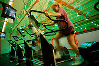 Blurred motion image of young women watching television as they exercise on treadmills at a gym fitness center.