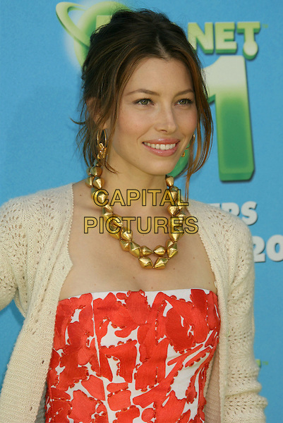 "JESSICA BIEL.At The Premiere of Columbia Pictures ""Planet 51"" held at The Mann Village Theatre, Westwood, California, USA, 14th November 2009..portrait headshot red orange and white print pattern beige cream knitted pointelle cardigan chunky gold necklace hair up hoop earrings .CAP/ADM/MJ.©Michael Jade/AdMedia/Capital Pictures."