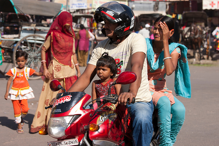 Indian family riding motorcycle, street scene at Sardar Market at Girdikot, Jodhpur, Rajasthan, Northern India