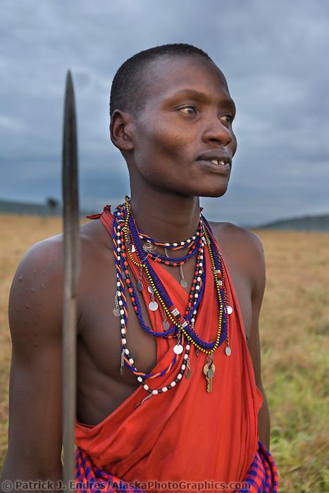 Portrait of a Masai tribesman at dawn holding a spear in the Masai Mara, Kenya, Africa