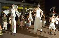 Walking on stilts, Kristen Greco (left) and Anson Smith, of the Carpetbag Brigade, take part in the Parade of Little Angels Saturday night. The event was part of All Souls Procession festivities and took place at the downtown main library, 100 North Stone Ave.