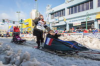 Isabelle Travadon and team leave the ceremonial start line with an Iditarider at 4th Avenue and D street in downtown Anchorage, Alaska during the 2015 Iditarod race. Photo by Jim Kohl/IditarodPhotos.com