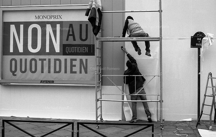 Paris (&icirc;le de france)<br /> <br /> Hommes en train de travailler a cote d`un panneau publicitaire de monoprix.<br /> <br /> Men working beside a billboard `s monoprix.