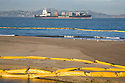 Oil containment booms (yellow) line the sands and waters of Crissy Field as a loaded Horizon Lines container ship enters San Francisco Bay (11/12/07). On November 7, 2007 the Cosco Busan container ship spilled an estimated 58,000 gallons of bunker fuel into San Francisco Bay after striking a tower of the San Francisco-Oakland Bay Bridge.