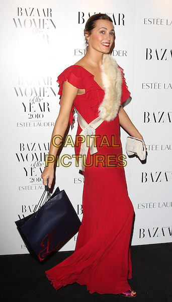 YASMIN LE BON.Harper's Bazaar Women of the Year Awards at One Mayfair, London, England, UK, November 1st 2010..full length red long maxi dress beige fur sash white clutch bag ruffle ruffles  hair up cream .CAP/ROS.©Steve Ross/Capital Pictures