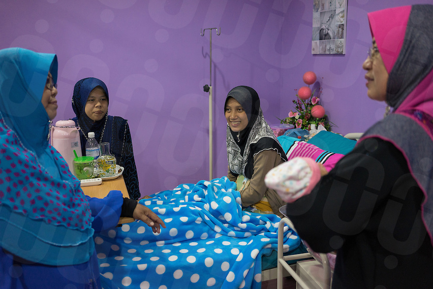 January 10, 2015 - Rawang (Malaysia). Dr. Azlina Jamaluddin (right) visits a friend, Nik Raihana (27), who delivered a baby the day before at the Global Ikhwan clinic. Despite been living in Kedah, five hours drive from Rawang, she chose to deliver her first daughter at the company's clinic. © Thomas Cristofoletti / Ruom