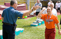 Happy medal winner high fiving policeman. Special Olympics U of M Bierman Athletic Complex. Minneapolis Minnesota USA