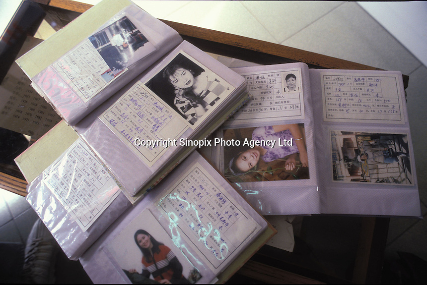 Books of women for potential brides at a Dating Agency in Guangzhou, China. An average gender inbalance 118 males to 100 females caused by the strict One Child Policy and the preference for boys means that there is a shortage of women in China.