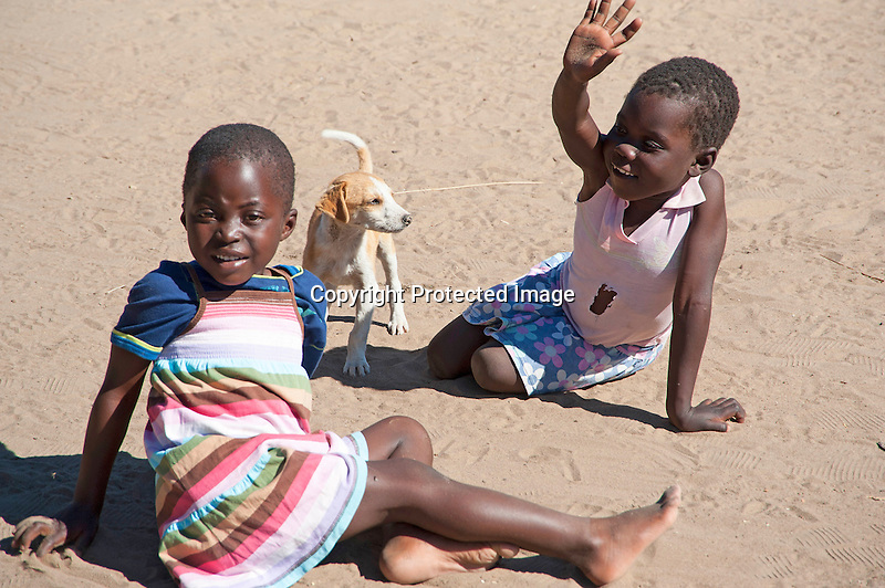 Two Young Children and Dog in Yard in Rural Ziga Village in Zimbabwe