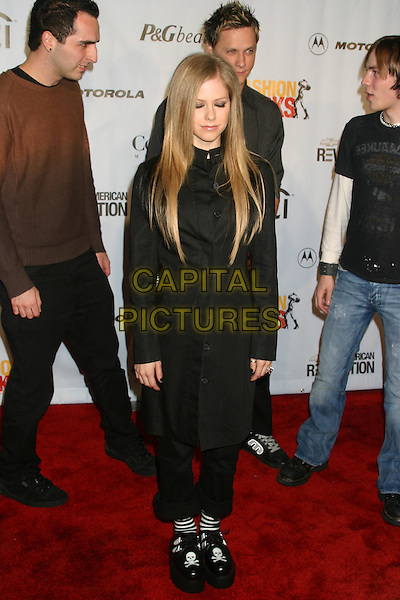 AVRIL LAVIGNE.Conde' Nast Media Group Presents Fashion Rocks 2004   Radio City Music Hall in New York City..September 8, 2004 .full length, eyes closed, black jacket, skull and cross bones shoes, striped socks.www.capitalpictures.com.sales@capitalpictures.com.© Capital Pictures