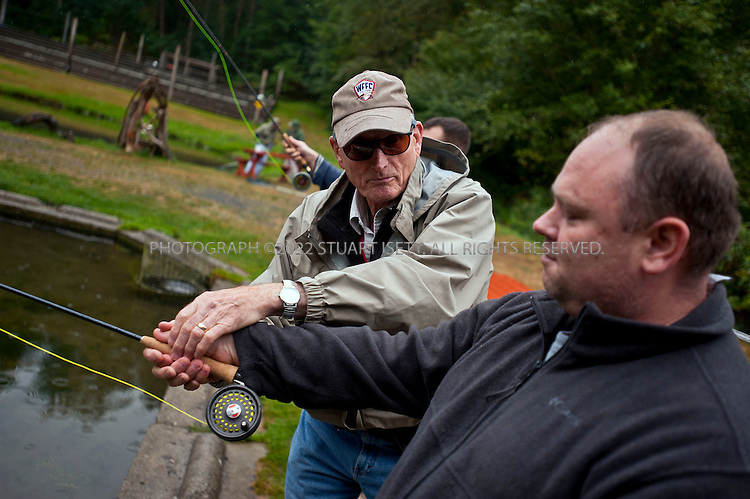 """9/17/2011--Orting, WA, USA..Jim McRoberts, a veteran and member of Healing Waters, helps teach Guy Naylor, 42, from Rockaway, OR, fly fishing. Nayor is an army veteran, and spent a day learning fly fishing at Bill's Fly Fishing Hole in Orting. WASH., about an hour's drive from Seattle. Naylor is currently an inpatient at the VA's hospital in Seattle suffering from Post Traumatic Stress Disorder (PTSD)...Healing Waters is a national nonprofit organization, founded to help disabled active-duty personnel and veterans by helping them, at no cost, to relearn fine motor skills and connect with other veterans, simply by learning the art of fly-fishing. It's an example of the kind of out-of-the-box thinking that is going into battling the devastating psychological effects of war. Some Healing Waters participants are in wheelchairs, missing limbs or just struggling with the transition to civilian life. Some suffer from PTSD, a condition that many say is like reliving hell. ..PTSD is an anxiety disorder brought on by a traumatic, life-threatening event. It is prevalent among combat veterans, but can also be experienced by civilians, including survivors of assault, rape, terrorist attacks, natural disasters and even extreme car accidents. Experts sometimes refer to it as the """"signature wound"""" of our current conflicts in Iraq and Afghanistan, although statistics on the number of soldiers with PTSD remain vague. Studies report that it can occur in anywhere between 5 and 35 percent of soldiers returning from combat - or """"theater"""" as it is referred to in the military. In 2010, 171,423 deployed Iraq and Afghanistan war veterans were diagnosed with PTSD, out of593,634 patients treated by the VA--nearly one-third of them. And it's likely that diagnoses will continue to increase due to current soldiers experiencing multiple deployments--and thus, potentially longer exposure to trauma....©2011 Stuart Isett. All rights reserved."""
