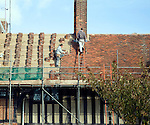 Men re-roofing  historic building with clay tiles, Thorpeness, Suffolk, England