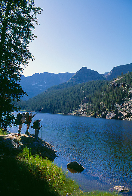 Hikers stand at edge of Lake Verna, Rocky Mtn Nat'l Park, CO